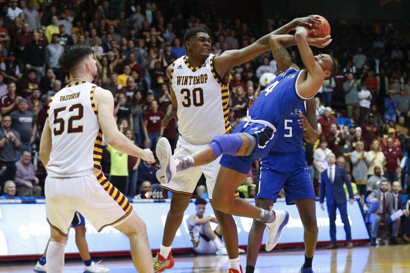 Winthrop forward D.J. Burns (30) fouls Hampton guard Greg Heckstall as Winthrop guard Chandler Vaudrin (52) looks on in the second half in the Big South tournament championship in Rock Hill, S.C. on Sunday.