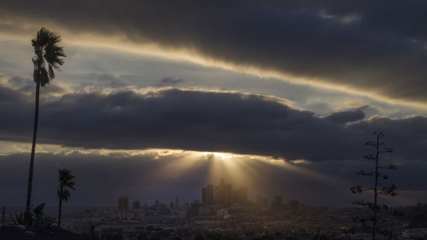 A storm settles over downtown Los Angeles in 2017. An atmospheric river that could wreak havoc by unleashing floods and landslides is set to arrive in Southern California on Tuesday night.