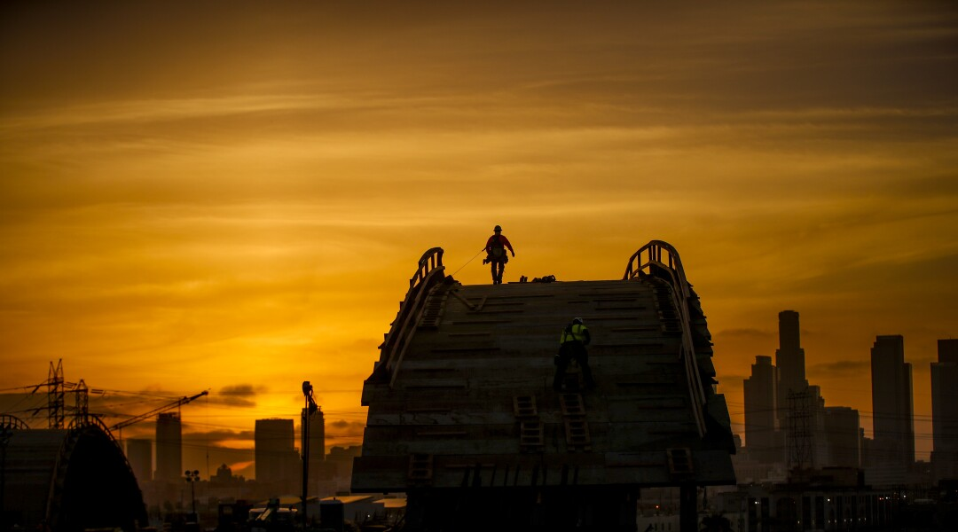 A worker walking at the top of an arch is silhouetted by the setting sun