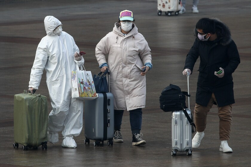 A passenger wearing a full-body protective suit at the Beijing railway station on Tuesday.