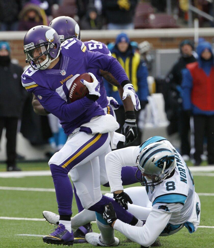 Minnesota Vikings wide receiver Adam Thielen (19) runs from Carolina Panthers punter Brad Nortman (8) as he returns a blocked punt for a touchdown during the first half of an NFL football game, Sunday, Nov. 30, 2014, in Minneapolis. (AP Photo/Ann Heisenfelt)