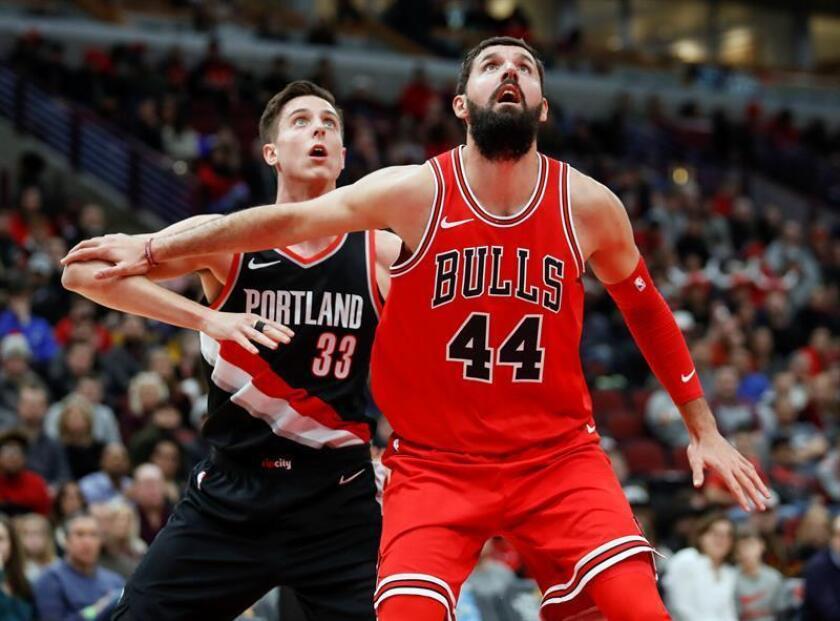 Nikola Mirotic (d) de Bulls disputa el balón ante Zach Collins (i) de Trail Blazers, durante su juego de la NBA en el United Center en Chicago, Illinois (EE.UU.). EFE