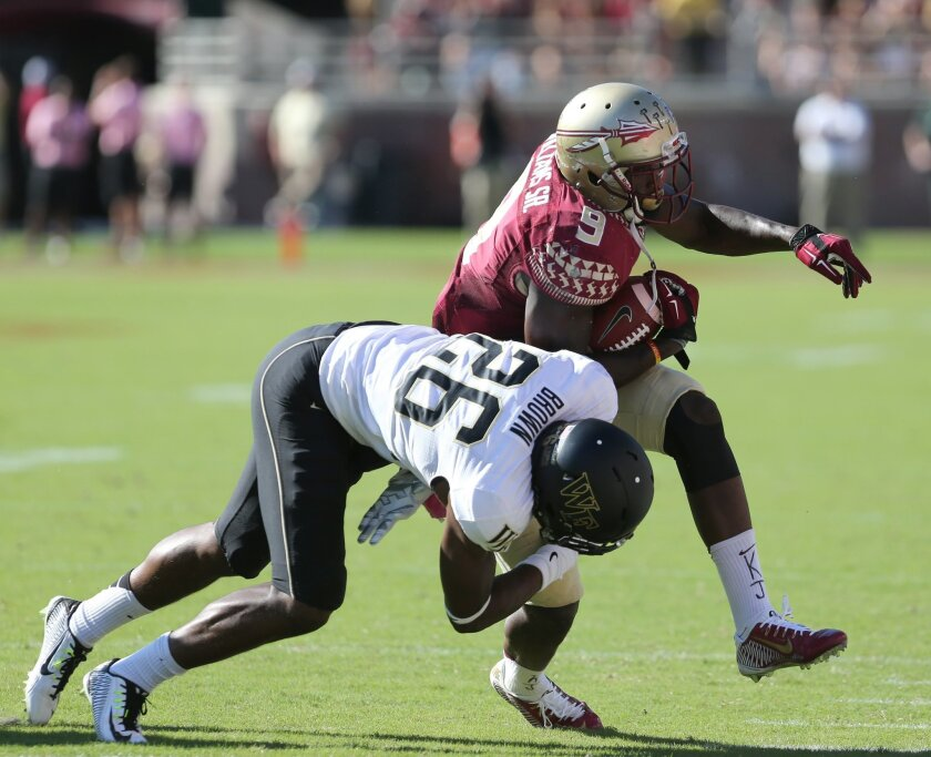 Florida State's Karlos Williams is knocked out-of-bounds by Wake Forest's Thomas Brown during the second quarter of an NCAA college football game, Saturday Oct. 4, 2014 in Tallahassee, Fla. (AP Photo/Steve Cannon)
