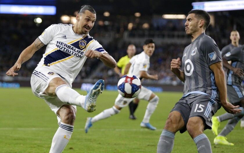 Galaxy forward Zlatan Ibrahimovic attempts a shot while defended by Minnesota's Michael Boxall during the first half Sunday.