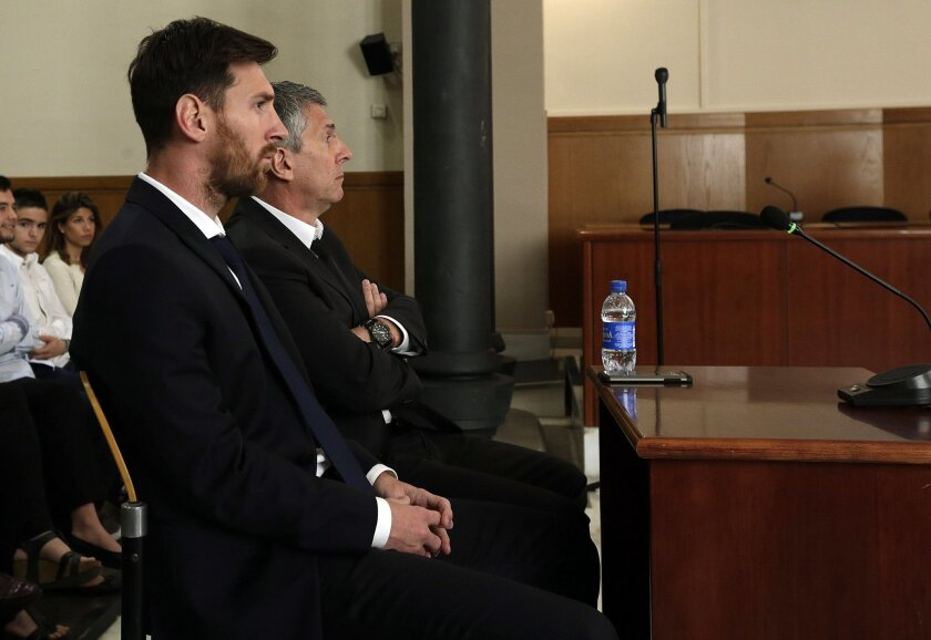 Barcelona's Lionel Messi, foreground, and his father Jorge Horacio Messi sit in court in Barcelona, Spain, Thursday June 2, 2016. Lionel Messi denied having knowledge of the tax issues that led to fraud charges against him, saying Thursday he signed documents without reading them because he trusted