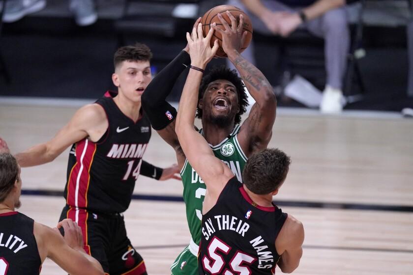 Kelly Olynyk (izquierda) y Duncan Robinson del Heat de Miami defienden