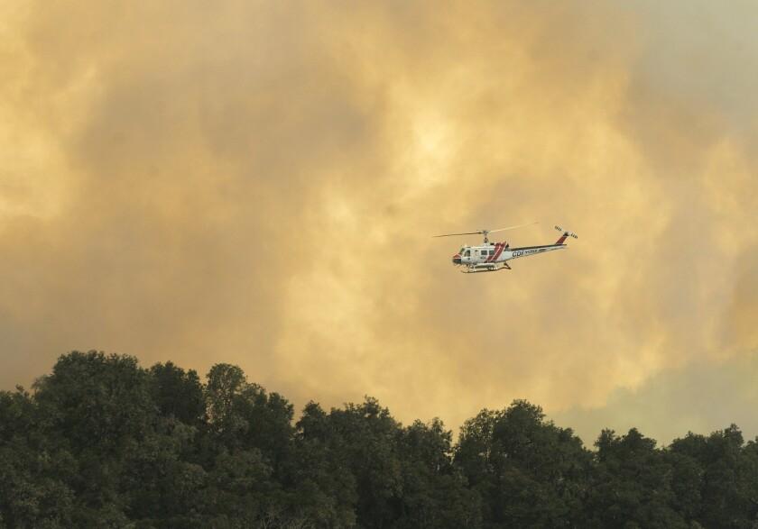 Un helicóptero de los bomberos se desplaza sobe un incendio forestal al suroeste de Cachagua, parte del esfuerzo para combatir el incendio Soberanes en el este del Valle de Carmel, en California, el lunes 1 de agosto de 2016. (David Royal/The Monterey County Herald vía AP) CREDITO OBLIGATORIO