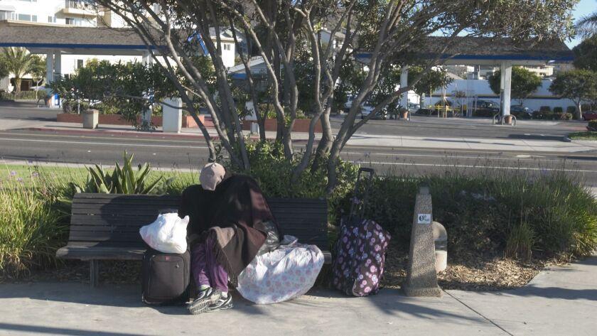 Thursday, Oct. 23, 2008. A homeless person sleeps on a public bench at Main Beach, Laguna Beach on T