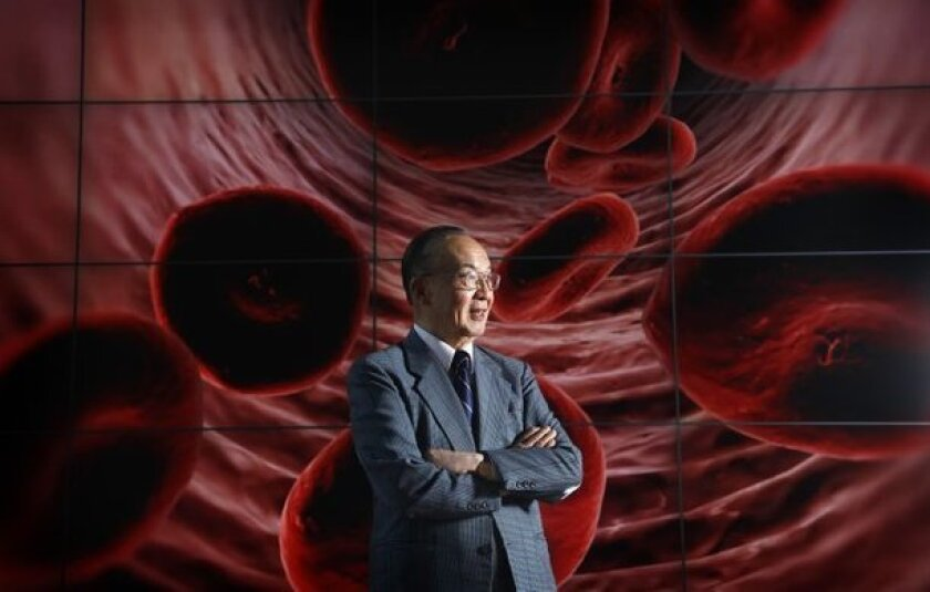 Shu Chien stands in front of an electronic image of red blood cells that was posted in a building at the UCSD Jacobs School of Engineering.