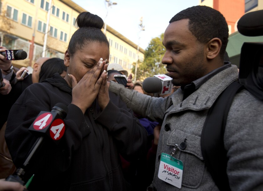 Nailah Winkfield, mother of 13-year-old Jahi McMath, is comforted by brother Omari Sealey as she talks to the media outside Children's Hospital Oakland.
