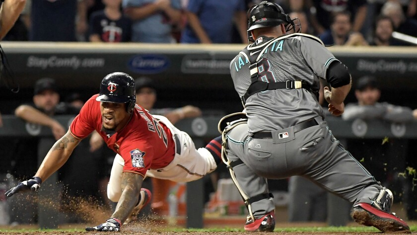 Twins center fielder Byron Buxton slides safely into home plate with an inside-the-park home run as Diamondbacks catcher Chris Iannetta fields a late relay throw during the fourth inning Friday.
