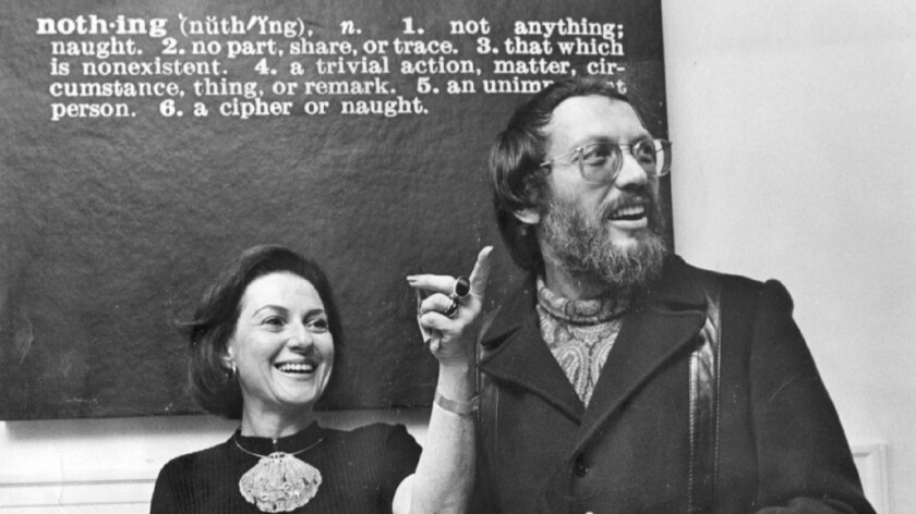 """Elyse and Stanley Grinstein greet guests for a 1972 party at their home under Joseph Kosuth's """"Nothing."""""""