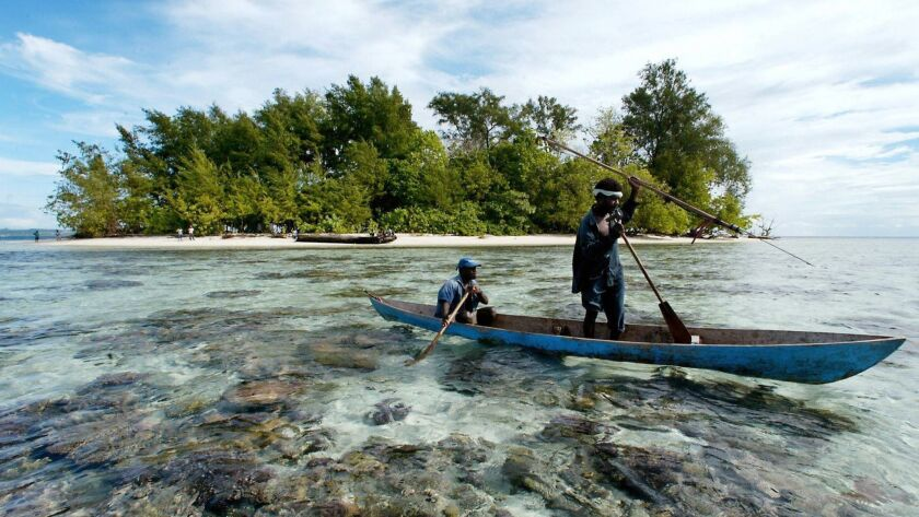 Fishermen paddle off the Solomon Islands