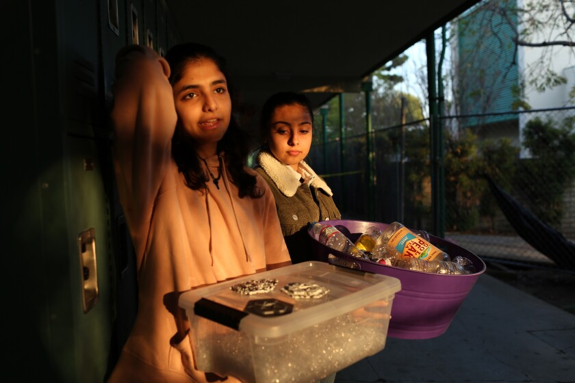 Coral Ben-Aharon, left, and Sarah Ali carry recycled plastic they are using for a project at Granada Hills Charter High School on Dec. 13 in Los Angeles. Chemistry teacher and science club advisor Jeanette Chipps incorporates climate change into her curriculum and projects.