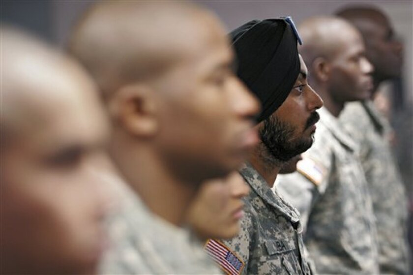 U.S. Army Spc. Simran Lamba, center, the first enlisted Soldier to be granted a religious accommodation for his Sikh articles of faith since 1984, stands in formation with fellow soldiers before taking the oath of citizenship, prior to his graduation from basic training at Fort Jackson, S.C., Wednesday, Nov. 10, 2010. (AP Photo/Brett Flashnick)