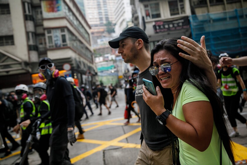 People watch emotionally as protesters retreat in Hong Kong ahead of advancing police.
