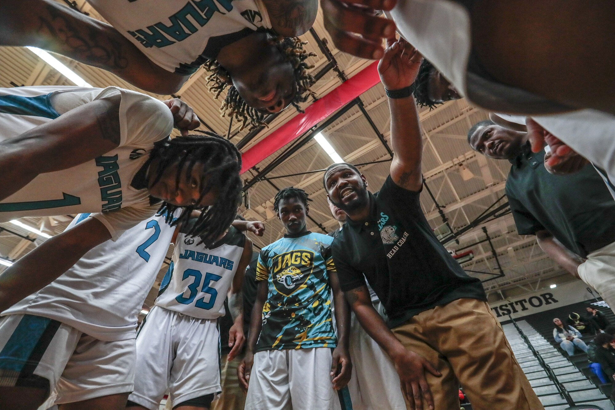 Flint coach Demarkus Jackson talks to his players during a game timeout.