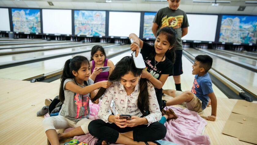 PORT ARTHUR, TEXAS -- THURSDAY, AUGUST 31, 2017: Fatima Flores, 12, center, gets her hair done by Sh