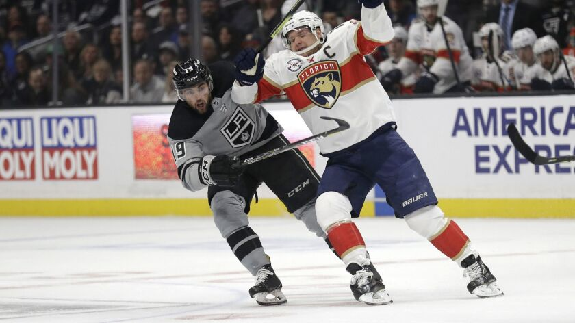 Florida Panthers captain Aleksander Barkov, right, and Kings forward Alex Iafallo chase after the puck during the first period of Saturday's game.