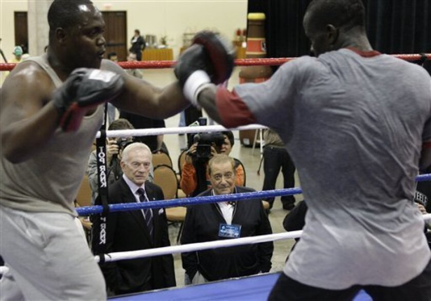Boxing promoter Bob Arum, center right, and Dallas Cowboys owner Jerry Jones, center left, watch Joshua Clottey, right, work out with Bismarck Bruce in Grapevine, Texas, Monday, March 8, 2010. Clottey is scheduled to fight Manny Pacquiao in a welterweight title bout this weekend at Cowboys Stadium in Alrington, Texas. (AP Photo/LM Otero)
