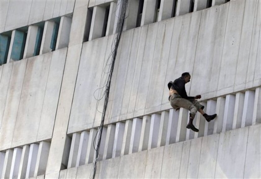 A man jumps from a building that caught on fire in Lahore, Pakistan, Thursday, May 9, 2013. The 13-storey government building caught fire and quickly intensified spreading to three floors of the tall building. (AP Photo/K.M. Chaudary)