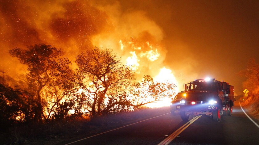 Fire personnel drive along West Lilac Road near Bonsall as the Lilac Fire burns on Thursday, Dec. 7, 2017. (Photo by K.C. Alfred/The San Diego Union-Tribune)