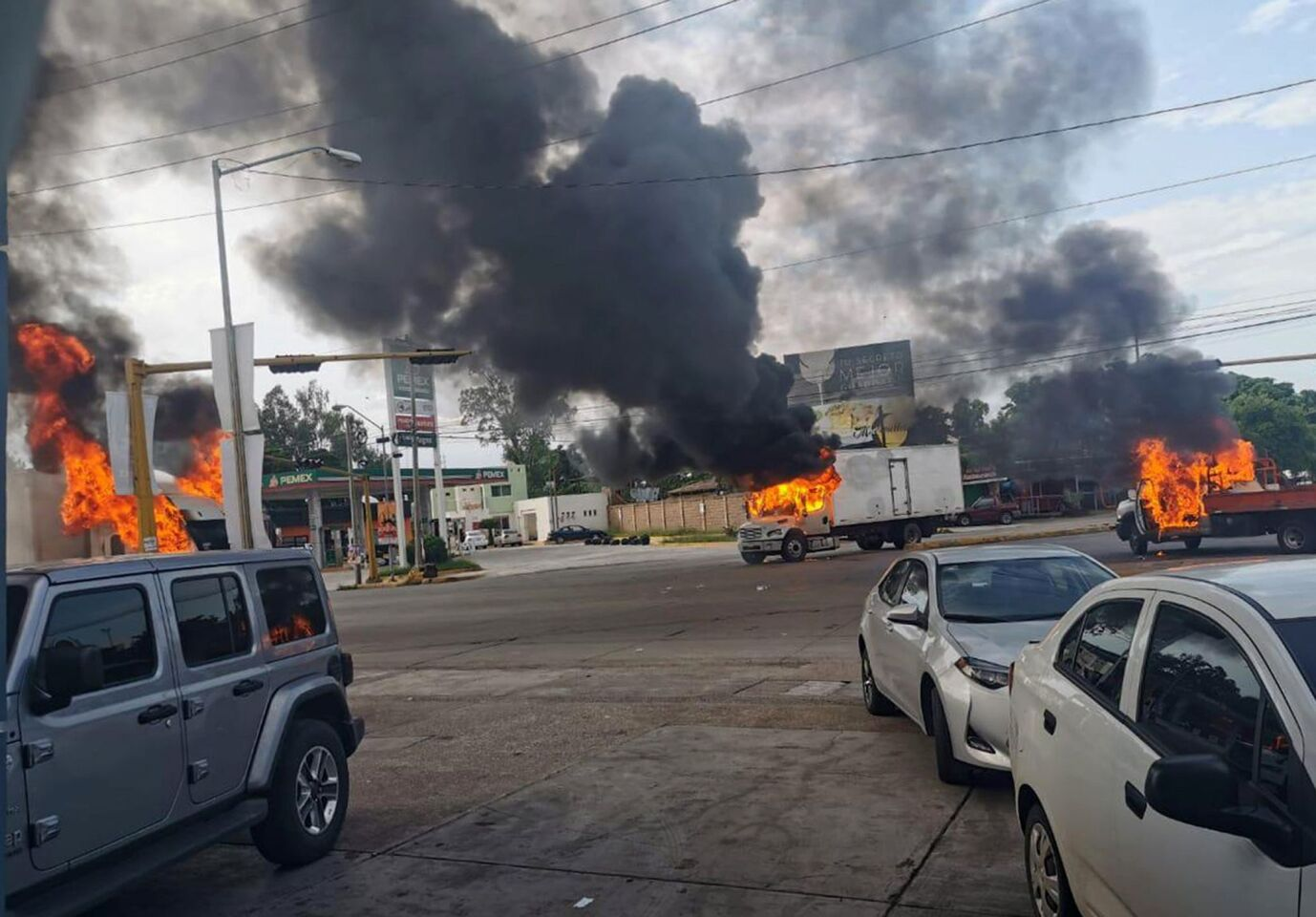 Mandatory Credit: Photo by STR/EPA-EFE/REX (10449104a) A view of vehicles on fire during a clash between armed gunmen and Federal police and military soldiers, in the streets of the city of Culiacan, Sinaloa state, Mexico, 17 October 2019. According to media reports, alleged drug cartel gunmen set up blockades and unleashed volleys of gunfire in the Mexican city of Culiacan amid rumors of the capture of Ovidio Guzman Lopez, son of imprisoned drug trafficker Joaquin 'El Chapo' Guzman Loera. The blockades set up by the gunmen, presumably from the Sinaloa drug cartel, extended to the exits of the city. Attempted capture of Ovidio Guzman Lopez sparks gunbattle in Culiacan, Mexico - 17 Oct 2019 ** Usable by LA, CT and MoD ONLY **