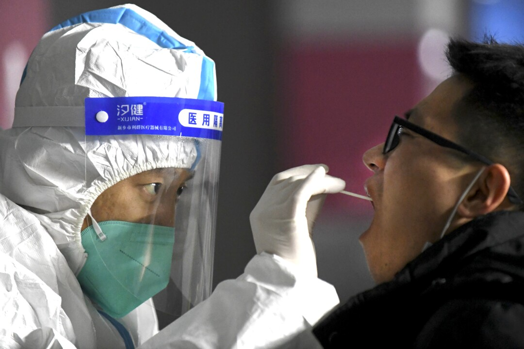 A medical worker in a protective suit takes a swab from a resident in Shijiazhuang, China.