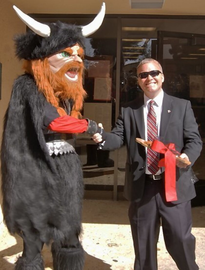 La Jolla High's new principal, Dr. Chuck Podhorsky, is given the key to the school by its Viking mascot. Courtesy