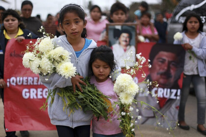 The granddaughters of slain journalist Gregorio Jimenez walk towards the cemetery in Coatzacoalcos, Mexico, Wednesday Feb. 12, 2014. Veracruz state officials concluded that Jimenez, a police beat reporter, was killed in a personal vendetta, unrelated to his reporting. But journalists throughout Mex