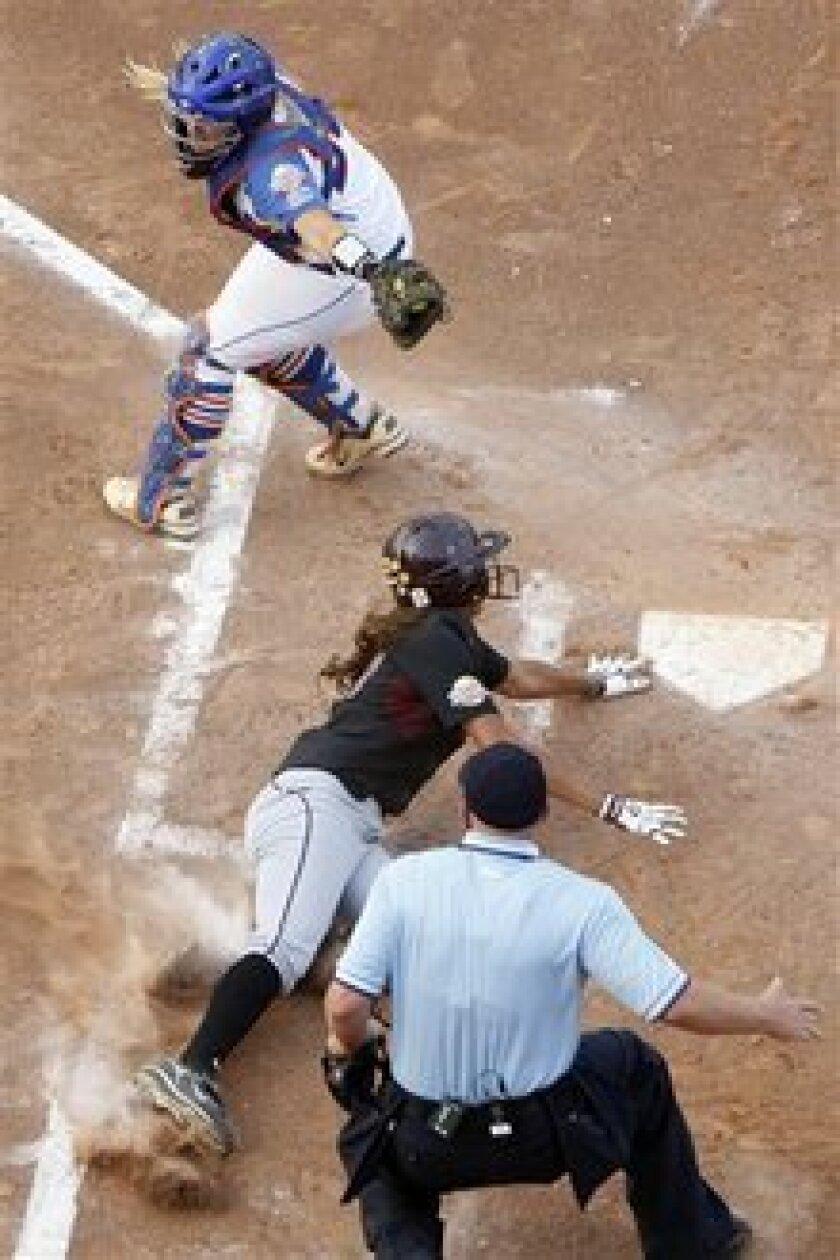 Home plate umpire Paul Edds watches the play as Arizona State's Alix Johnson slides safely into home plate, avoiding the tag of Florida catcher Tiffany DeFelice in the second inning of a Women's College World Series championship series game in Oklahoma City.