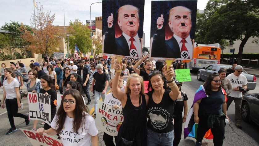 Demonstrators in Los Angeles hold placards depicting President-elect Donald Trump as Hitler, as thousands march in reaction to the presidential election results on Nov. 12.