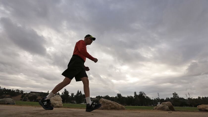 John Osmundson gets his speed walk in under foreboding skies as people work out around the Rose Bowl on Wednesday morning before a rainstorm was expected to hit.