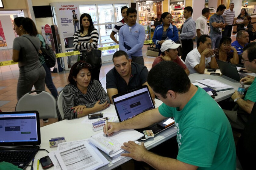 People purchase health insurance under the Affordable Care Act at a kiosk at a mall in Miami earlier this year.