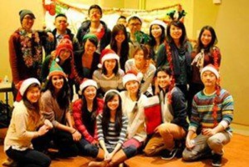 Members of Alpha Phi Omega, a UC San Diego service fraternity, dress in festive attire while wrapping presents and working on the Operation Santa project. Courtesy Photos