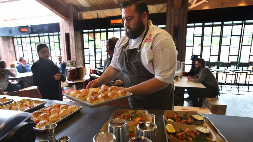 Andrew Shrader, head chef at the new Encinitas Crack Shack restaurant, carries out trays of fresh-baked biscuits.