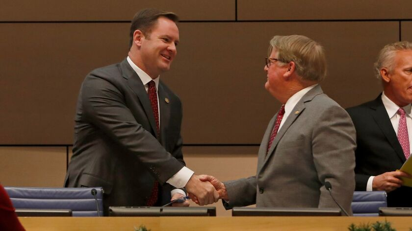 New Newport Beach Mayor Pro Tem Will O'Neill, left, shakes hands with new Mayor Duffy Duffield as th