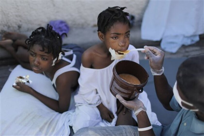 An injured girl is feed by a hospital volunteer at the general hospital in Port-au-Prince, Saturday, Jan. 16, 2010. Relief groups and officials are focused on moving aid flowing into Haiti to survivors of the powerful earthquake that hit the country on Tuesday. (AP Photo/Ariana Cubillos)