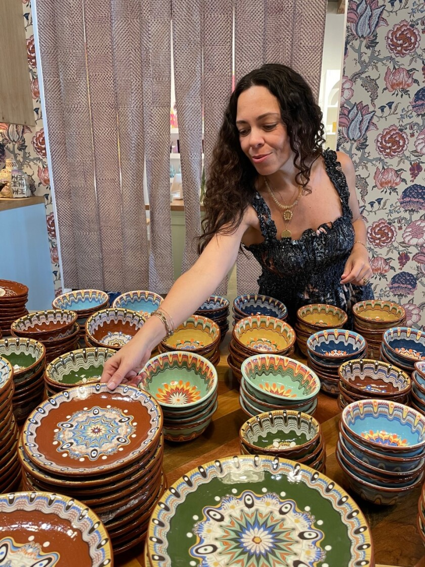 A woman arranges colorful ceramic plates and bowls on a table.