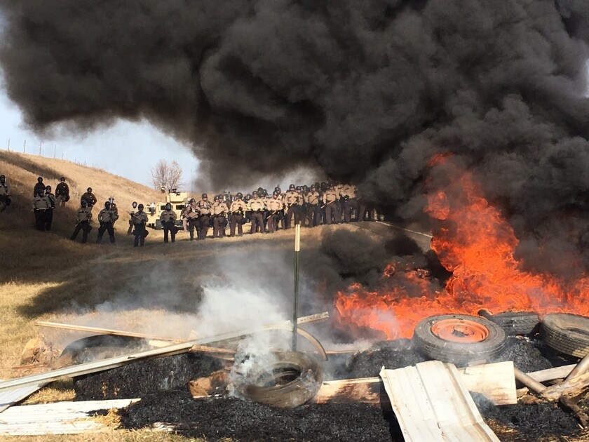Tires burn as soldiers and law enforcement officers stand in formation to force Dakota Access pipeline protesters off private land in Morton County, N.D.