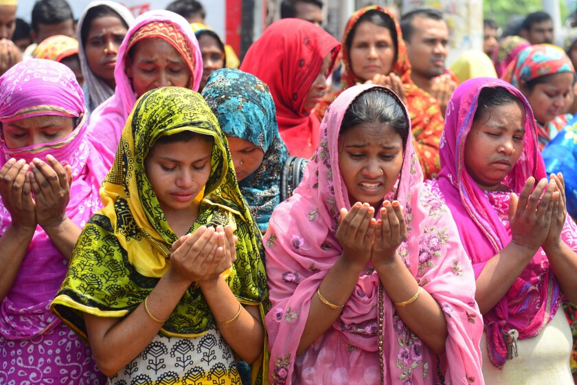 Family members of missing garment workers offer prayers in front of the rubble of a factory building that collapsed on the outskirts of Dhaka, Bangladesh.