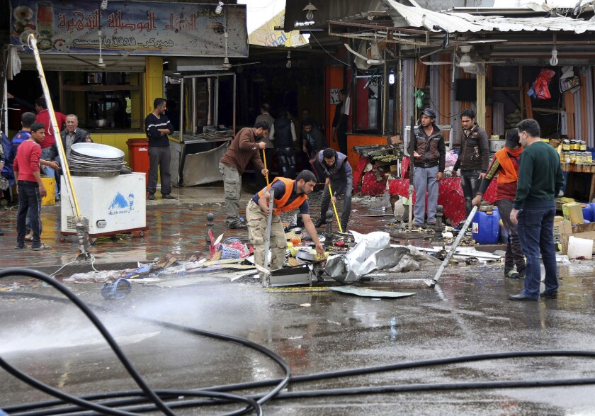 Iraqis clean the streets after a suicide bombing in New Baghdad. It was the deadliest of three bombings Saturday.