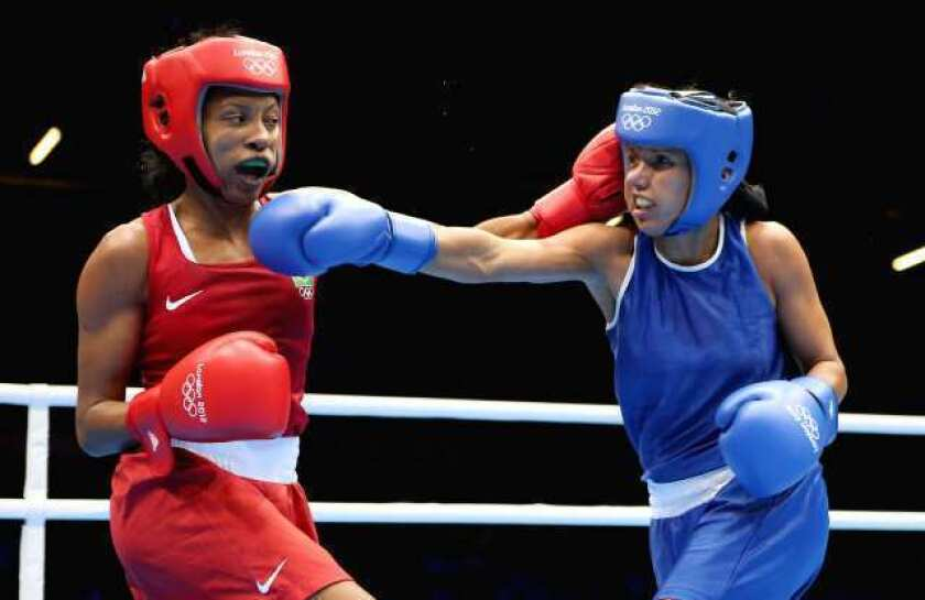 Karlha Magiliocco of Venezuela, right, in action with Erica Matos of Brazil during the debut of women's boxing at the Olympics on Sunday.