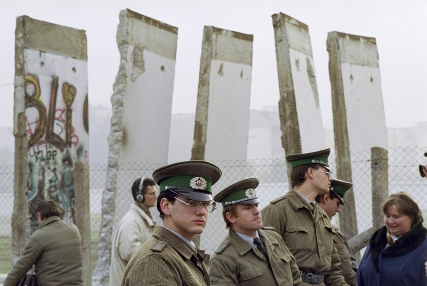 """FILE - In this Nov. 13, 1989, file photo, East German border guards stand in front of segments of the Berlin Wall, which were removed to open the wall at Potsdamer Platz passage in Berlin. Months before the Berlin Wall fell on Nov. 9, 1989, with the Soviet stranglehold over the Eastern Bloc crumbling, a young political scientist named Francis Fukuyama made a declaration that quickly became famous. It was, he declared, """"the end of history."""" (AP Photo/John Gaps III, File)"""