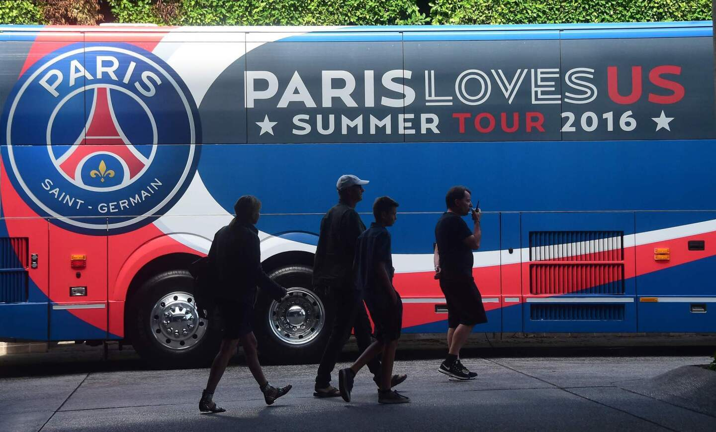 Pedestrians walk past the Paris Sant-Germain team bus transporting players to a training session at Loyola Marymount University in Los Angeles, California on July 26, 2016, one day ahead of their International Champions Cup soccer match against Real Madrid in Columbus, Ohio. The squad will return to California following that encounter for a July 30 match against Leicester City in Carson, California. / AFP PHOTO / Frederic J. BROWNFREDERIC J. BROWN/AFP/Getty Images ** OUTS - ELSENT, FPG, CM - OUTS * NM, PH, VA if sourced by CT, LA or MoD **
