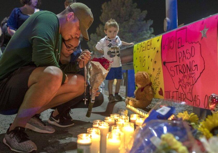 René Aguilar y Jackie Flores rezan en un memorial para las víctimas de un tiroteo en El Paso, Texas.