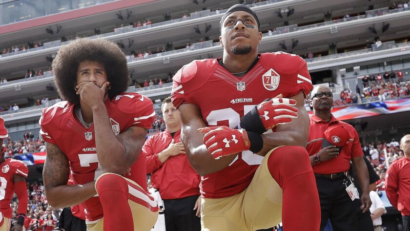 San Francisco 49ers quarterback Colin Kaepernick, left, and safety Eric Reid kneel during the national anthem before a game against the Dallas Cowboys on Oct. 2, 2016.