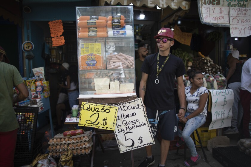 Signs promoting cheese, eggs and mortadella are displayed in a market in Caracas, Venezuela, Friday, June 11, 2021. (AP Photo/Ariana Cubillos)