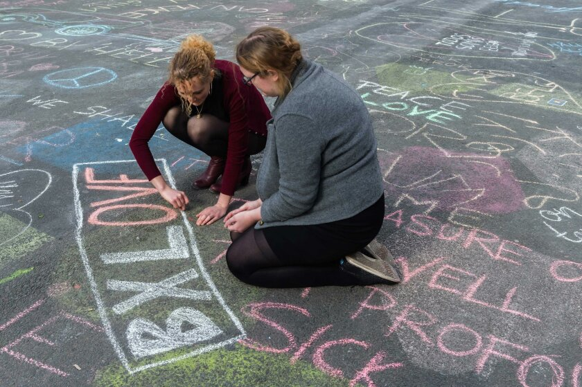 Two people write solidarity messages in chalk outside the stock exchange in Brussels on Tuesday, March 22, 2016. Explosions, at least one likely caused by a suicide bomber, rocked the Brussels airport and subway system Tuesday, prompting a lockdown of the Belgian capital and heightened security across Europe. At least 26 people were reported dead. (AP Photo/Geert Vanden Wijngaert)