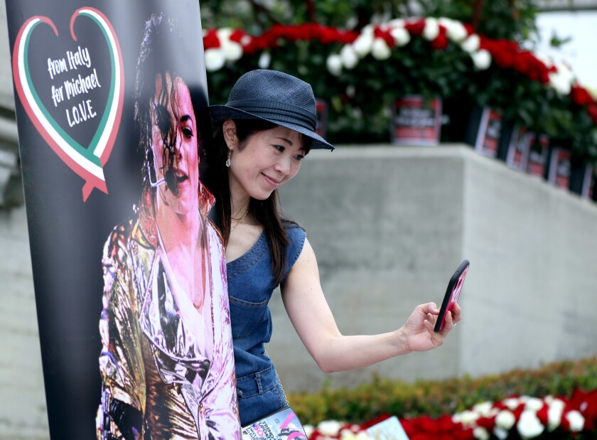Eriko Ono, 49, of Tokyo takes a selfie with a poster as hundreds of Michael Jackson fans gathered at Forest Lawn Cemetery in Glendale to pay tribute on the 10th anniversary of the death of the King of Pop on June 25, 2019.